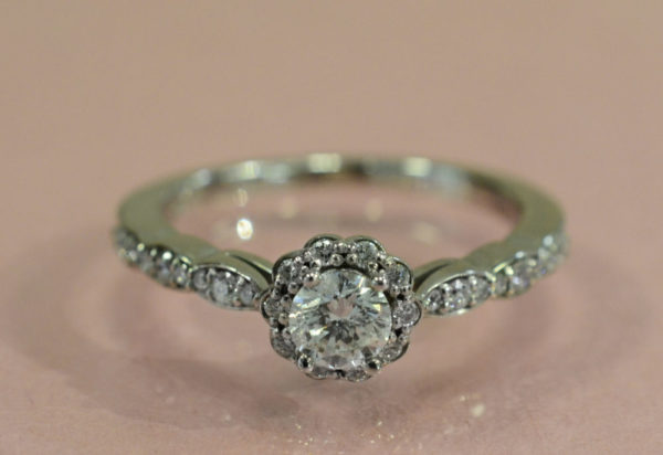 Diamond and 14K white gold halo style engagement ring on pink background