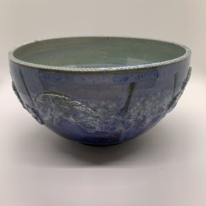 Ceramic bowl, glazed blue with a green interior, stamped and carved for decoration