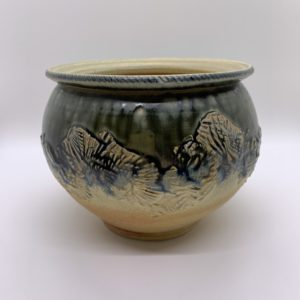 Green and khaki hand-made vessel. Carved and stamped for decoration