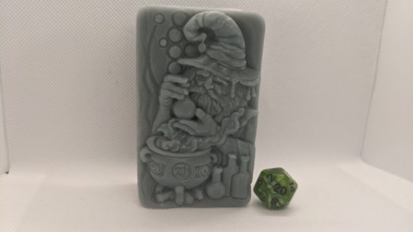 A molded bar of soap featuring a wizard working on a potion over a cauldron. This soap is olive green.
